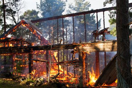 Huisruïne na brand, zichtbare vlammen en gloed