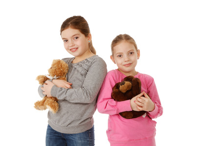 two girls hugging: Two girls hugging teddybears and smiling. Isolated.