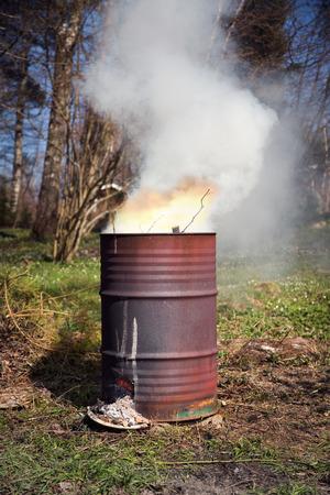 garden waste: Garden waste burning in old rusty barrel. Portrait format.