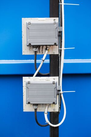 metal post: Two electrical box switches mounted on metal post against blue background. Stock Photo