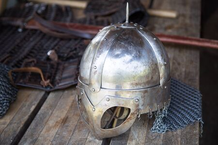 armament: Replika of Viking helmet with visible stroke marks on wooden table in front of hauberk and sword. Short depth of field.