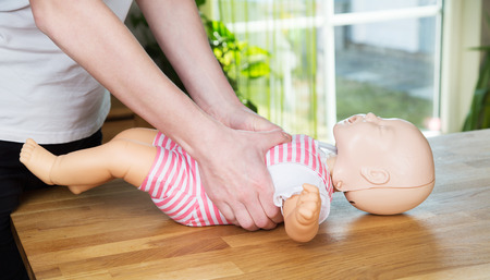 Woman performing CPR on baby training doll with two hands compressions