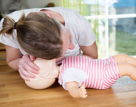 trẻ sơ sinh: Người phụ nữ thực hiện CPR trên con búp bê bé đào tạo, kiểm tra các dấu hiệu của hơi thở