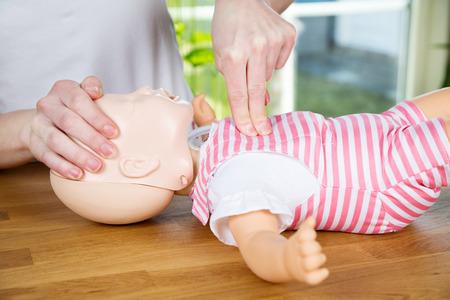massage bébé: femme d'effectuer la RCR sur baby doll de formation avec une compression de la main