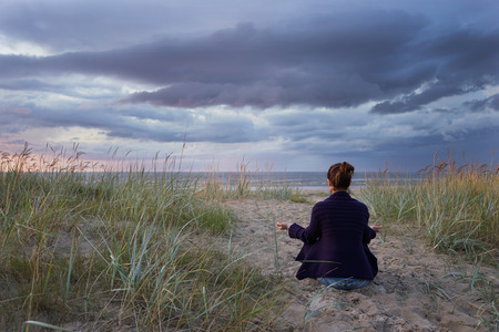 Woman meditates at the sea