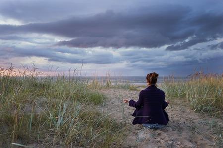 Woman meditates at the sea Banco de Imagens - 45693834