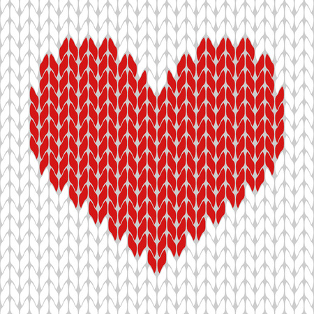 Knitted red heart on the white background