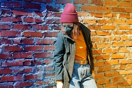 A sad girl in outerwear and a hat stands behind a brick wall in a black mask from the coronavirus