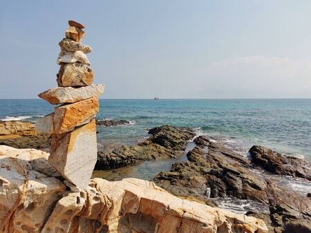 Balancing stones with each other on a rocky sea shore.