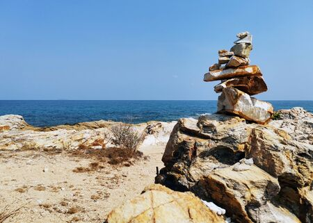 Balancing stones with each other on a rocky sea shore. Beautiful sea landscape