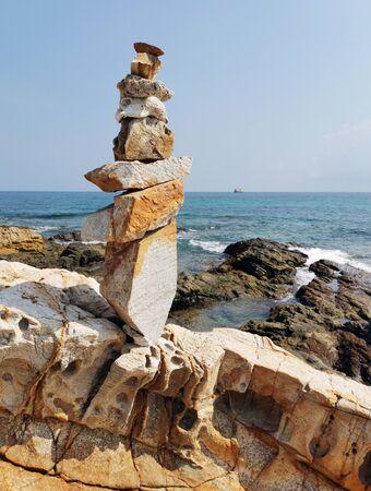Balancing stones on a rocky sea shore.