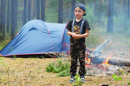 Tourist camping with tents in a pine forest. A small child-traveler on the background of a tent and a fire. Family adventure in nature. Banque d'images
