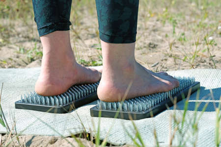 Close-up of women's legs in dark leggings standing barefoot on a bed of nails during a morning yoga practice. An exercise in balance, courage, and patience. Stock Photo