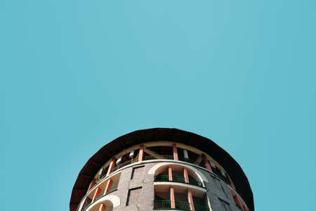 The roof of a circular building against a clear blue sky.
