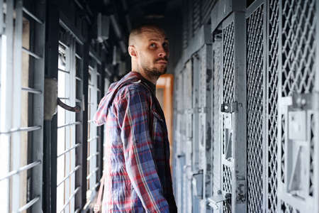 A man in a checked shirt stands in front of the entrance to a prison cell inside an old train. Banque d'images