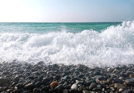 Stone coast of the Black sea. Strong wave on the stone shore. Background of sea stones. Sea coast of the South of Russia, Sochi