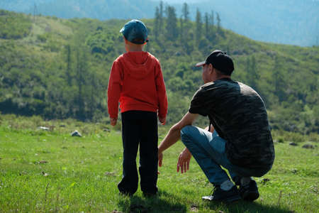 Father and son sit and stand on the grass and look into the distance against the background of the mountains. Summer photo about family and relationships