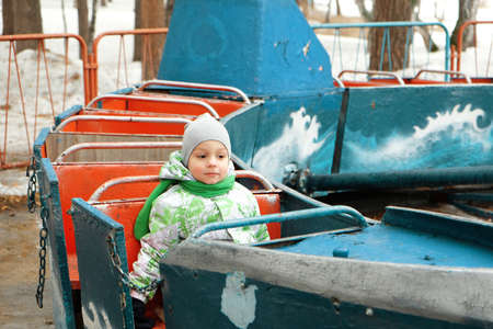 A little boy in a jacket and hat rides in a childrens open carousel train. Activity, impressions, emotions. The cold time of the year, snowy winter. Banque d'images