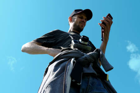 A man in a cap and with a camera around his neck looks at the phone against the sky. Bottom view.