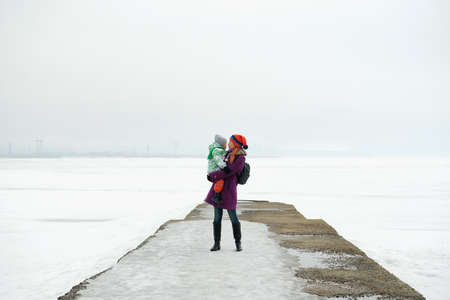 A mother holds her little son in her arms against the background of the frozen sea. Winter landscape, gray sky and white snow. Banque d'images