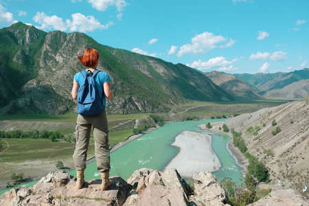 A young red-haired girl in a blue t-shirt with a backpack stands on a rock and looks towards the Katun river in the Altai mountains.