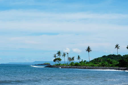 View of the ocean and a piece of the island with palm trees. Blue cloudy sky