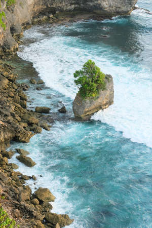 Top view of waves hitting the rocky shore. Turquoise color of the ocean. Stone island with a tree.