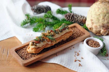 Unusual eclair with mushroom filling on a wooden tray with buckwheat. Siberian dessert