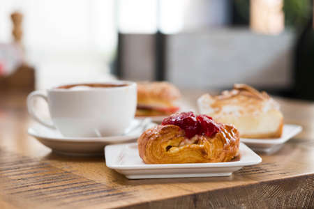 Puff pastry with berry filling on the background of buns and a cup of coffee. Morning composition on a wooden table. Serving breakfast