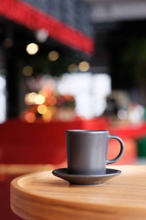 A small black coffee cup on a saucer on a wooden table. Coffee in a cafe on the background of blurred background
