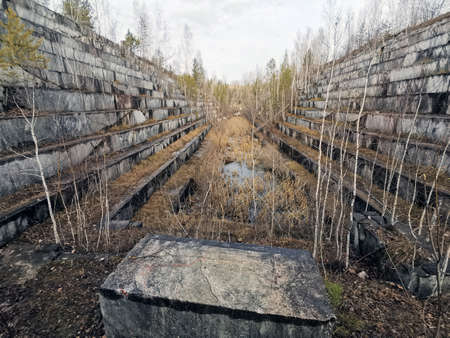 An abandoned marble quarry. Autumn landscape with a view of the overgrown steps of the old quarry. Banque d'images