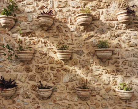 Clay stone wall made of shards and fragments of dishes and tiles. Vases pots with flowers from surface. Banque d'images