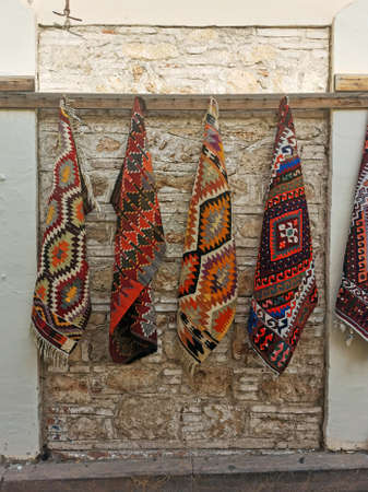Handmade carpets hung along the stone wall in the bazaar