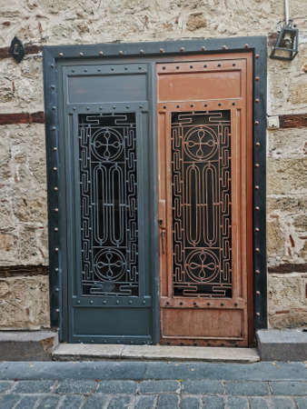 Metal door with beautiful carvings. Closed two-tone door on the background of a stone wall Banque d'images