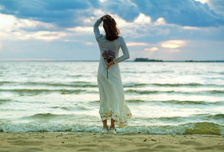 A girl in a white wedding dress stands with her back to the Stormy Sea. A conceptual picture about loneliness, hopes and expectations