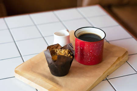 Top view of a red metal mug with black coffee, a chocolate muffin, and a white milk jug.