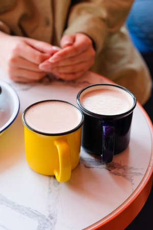 Two colored mugs with a hot drink and foam stand on the table against the background of womens hands.