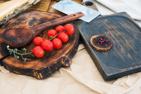 Fresh cherry tomatoes and spices on the wood and a chef's knife on the light surface of the table. Background of a modern restaurant kitchen with a copy space on a rustic cutting board, top view