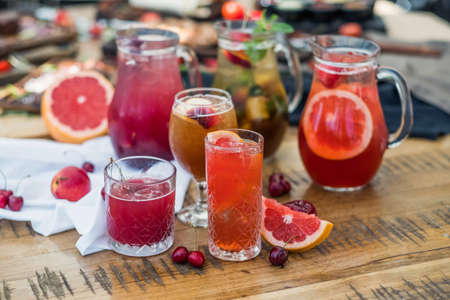 A composition of glass decanters and glasses with refreshing soft drinks made from fruits and berries.