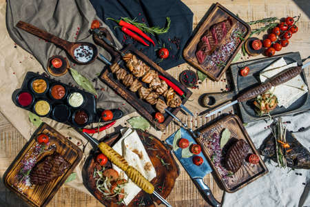 Flat composition with fried meat, shish kebab, steak, lula kebab and vegetables on a wooden table