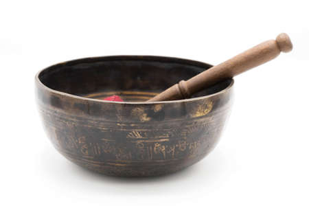 Handmade Tibetan Singing Bowl with a stick made of Dark Metal, Isolated on a White Background. Banque d'images