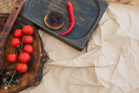 Fresh cherry tomatoes, chili peppers and spices on craft paper.