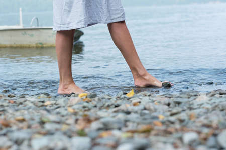 A girl walks along a rocky shore with bare feet, her feet in the water