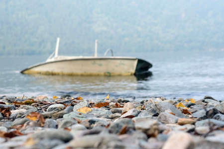 Beautiful landscape of the lake shore with a stone shore and an old boat Banque d'images