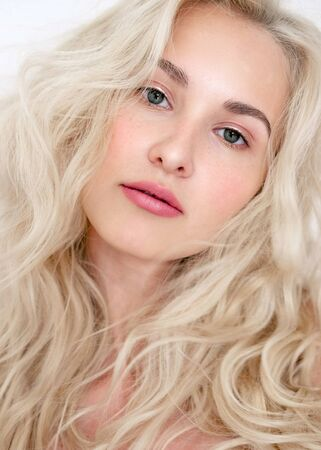 Portrait of a beautiful blonde model with lokans with natural makeup. Fashionable shiny marker on the skin, lip gloss, makeu