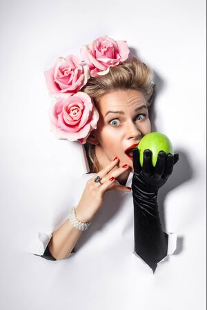 a cheerful woman makes a hole in white paper. A woman looks through a hole in a paper white background. A woman bites an Apple. A woman decorated in the Rococo style. Blonde with flowers in her hair. A woman in black gloves. Copy space for advertise.