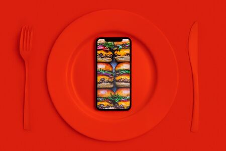 Order food online, food delivery. Call and theyll bring the food home. Smartphone with hamburgers on the screen, lying on a plate, a knife and fork. Red top View