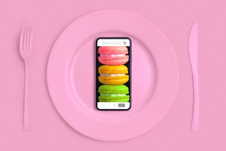 Food delivery to home buy via the Internet. Call them and theyll bring food home. Smartphone with macarons in an online store on the screen lying on a plate, knife and fork. The view from the top
