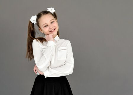 beautiful girl in a school uniform. Expression of happiness and joy. On gray background