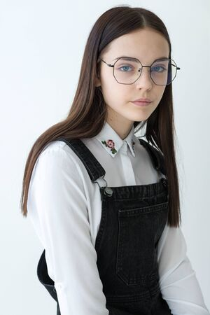 portrait of a beautiful teenage girl with glasses, An emotion of calm and joy. White background Reklamní fotografie